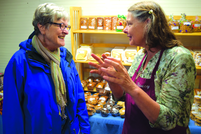 Mary Pat Marshall, left, of Aberdeen chats with Hoquiam's Nancy Lachel of Nancy's Bakery at the Grayland Cranberry Harvest Festival on Saturday.