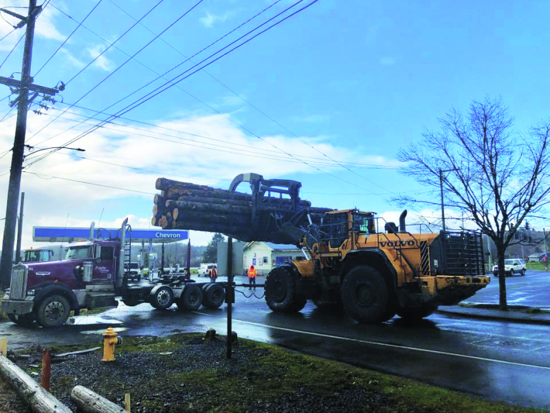 Photo Courtesy of Raymond Police Department - Weyerhaeuser stacker operator Jimmy Hardy carefully lifting the load of logs off the log truck.