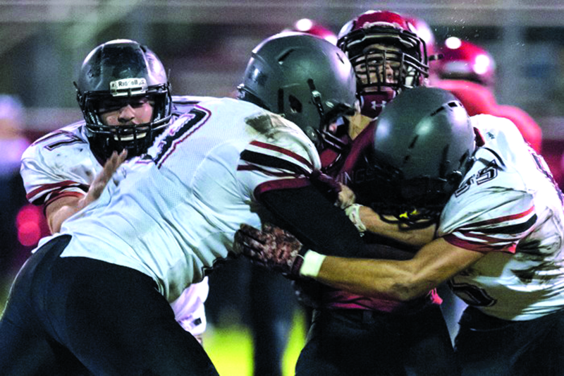 Photo by Jordan Nailon - Mossyrock's Bo Miles gang tackled by Indians Seth Nichols, Larry Demery, and Dalton Yoder.
