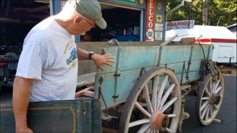 Photo by Laurie Bowman - Jerry Bowman examining the Mitchell wagon acquired by the Northwest Carriage Museum.