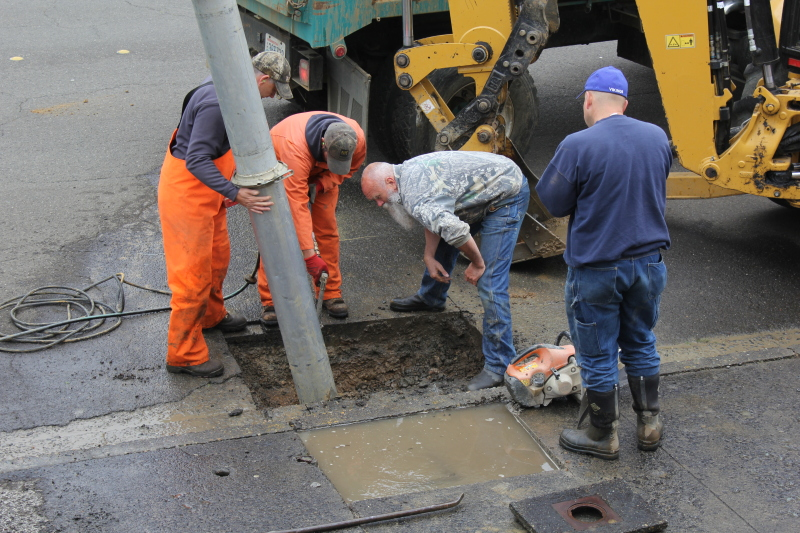 Photo by Patrick L Myers - Raymond Public Works hard at work on 4th Street in downtown Raymond where a service line had failed. The crew replaced a saddle on one of the pipes that had deteriorated as well as updated other old, possibly worn hardware.
