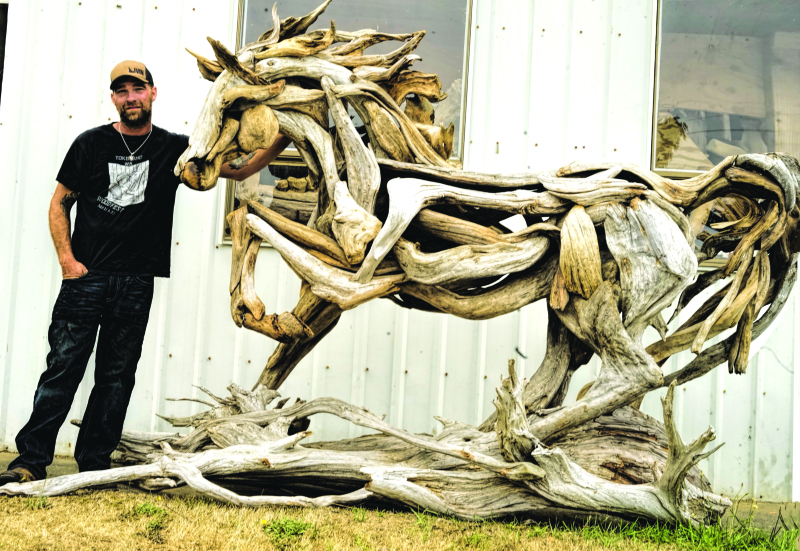 Photo by Marguerite Garth - Jeffro Uitto stands next to his driftwood horse at Woodfest in Tokeland. To see more of his artwork, visit his studio Knock on Wood at www.jeffrouitto.com.