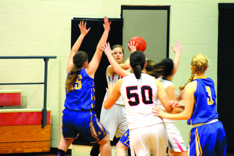 Photo by Kennedi Collins -  Haley Tauscher looks for an open teammate through the mob of Pirates.
