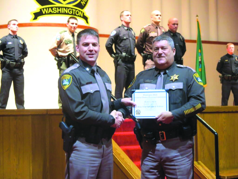 Photo Courtesy Chief Deputy Pat Matlock - Deputy Steve Ross (left) is awarded his diploma by Pacific County Sheriff Scott Johnson.