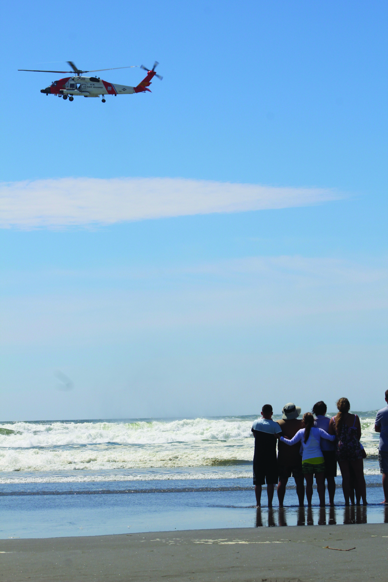 Photo by George Kunke - Family and friends watch as a Coast Air Station Astoria MH-60 Jayhawk searches for a 14-year-old boy in the ocean in Long Beach last Memorial Day.